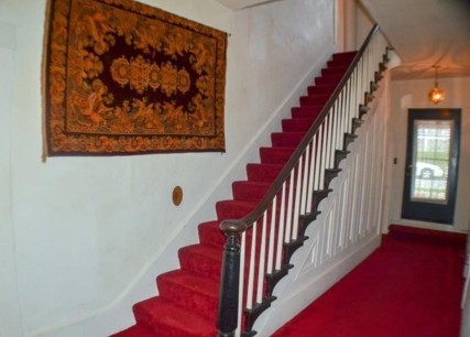 Grand staircase features side inlays and bent wood railings